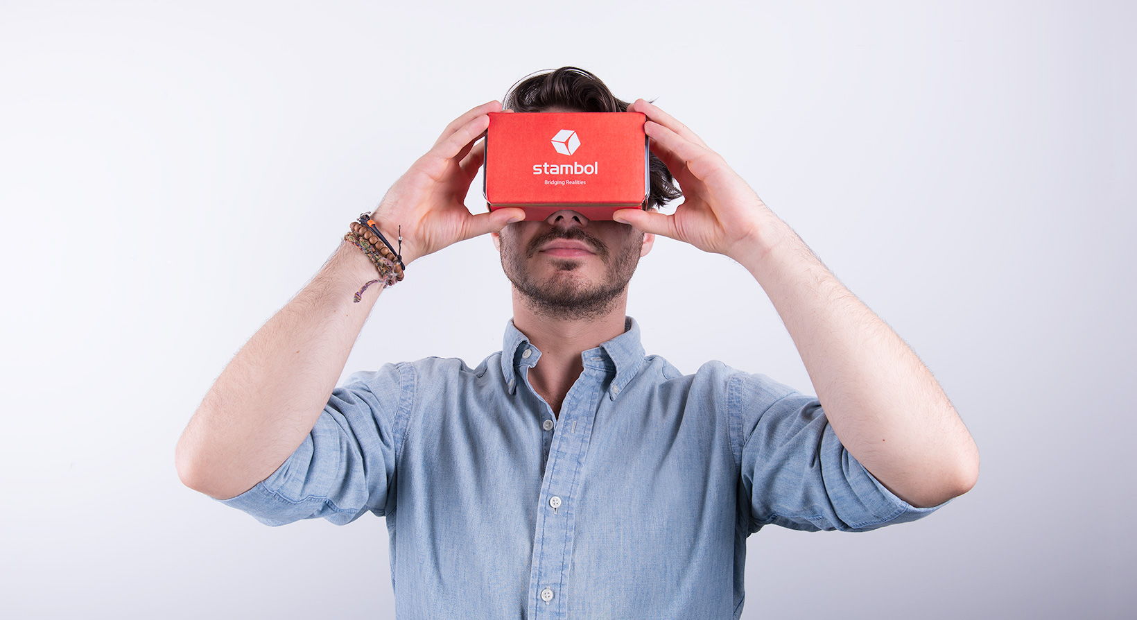male model holding Google Cardboard with Stambol logo