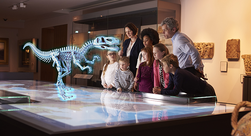 group of people at museum seeing dinosaur hologram on a map