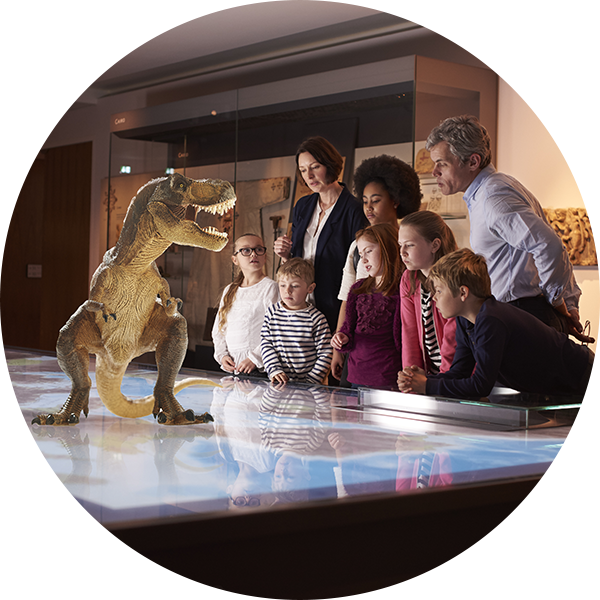 family watching hologram of a dinosaur at museum