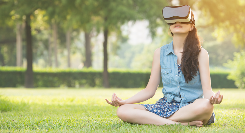 young female meditating with virtual reality headset in park