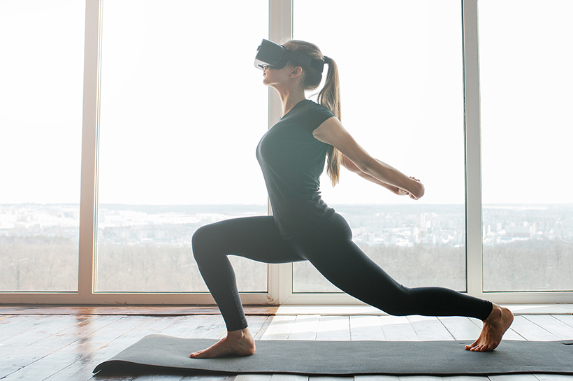 young woman doing yoga with a virtual reality headset