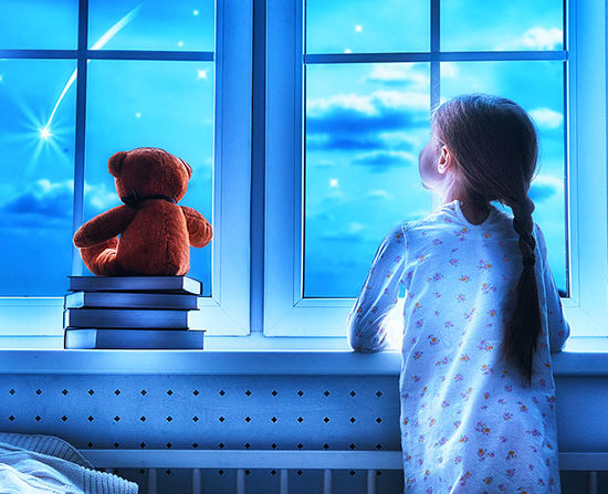 Girl making a wish by seeing a shooting star at bedtime night