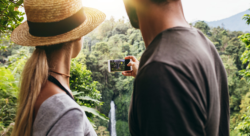 Young couple hiking and checking augmented reality app in their phone