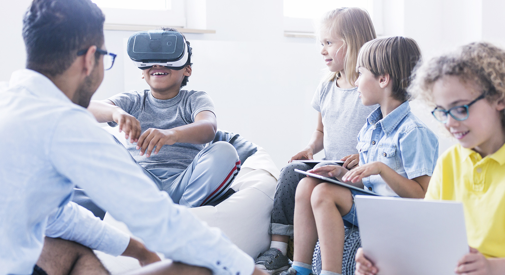 Kids with their teacher trying virtual reality and learning