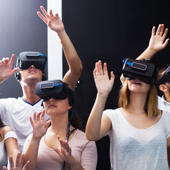 group of young people immersed into virtual reality experience