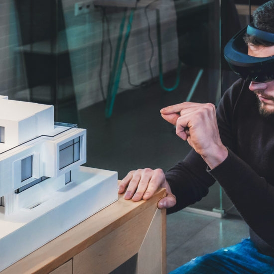 male architect working on a private house project in the office using augmented reality glasses