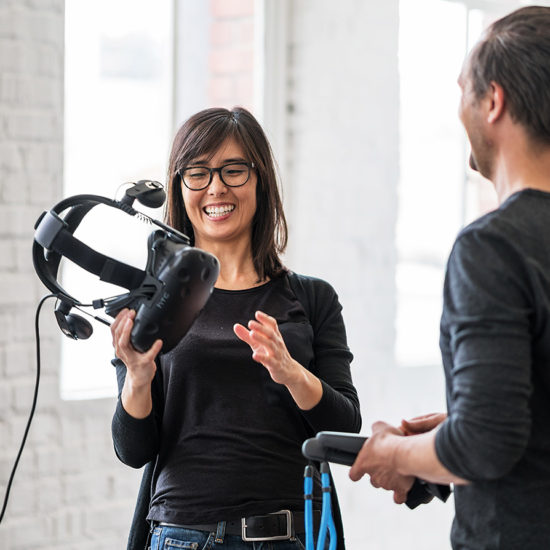 smiling female holding virtual reality headset and discussing with male engineer