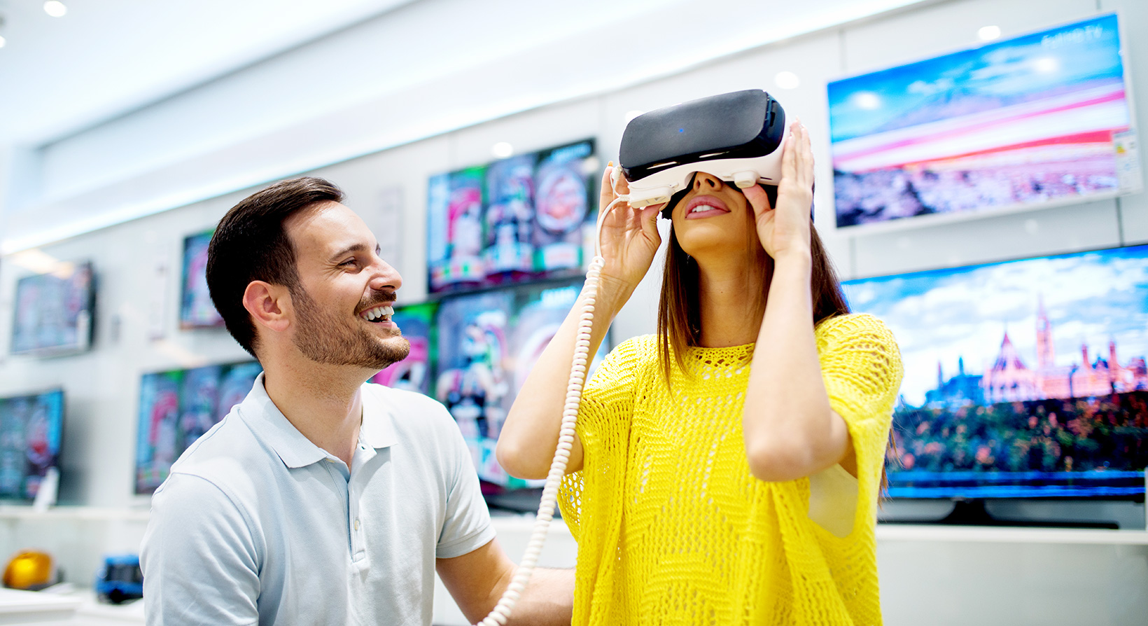 Young couple trying on virtual reality headset in a store