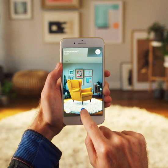 Male customer holding smart phone and decorating his room through IKEA AR App
