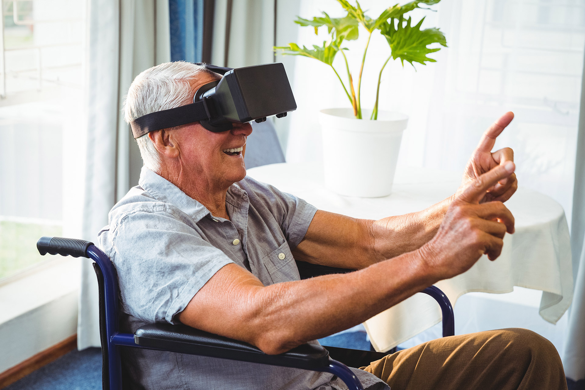 Senior man in a wheelchair using a virtual reality device
