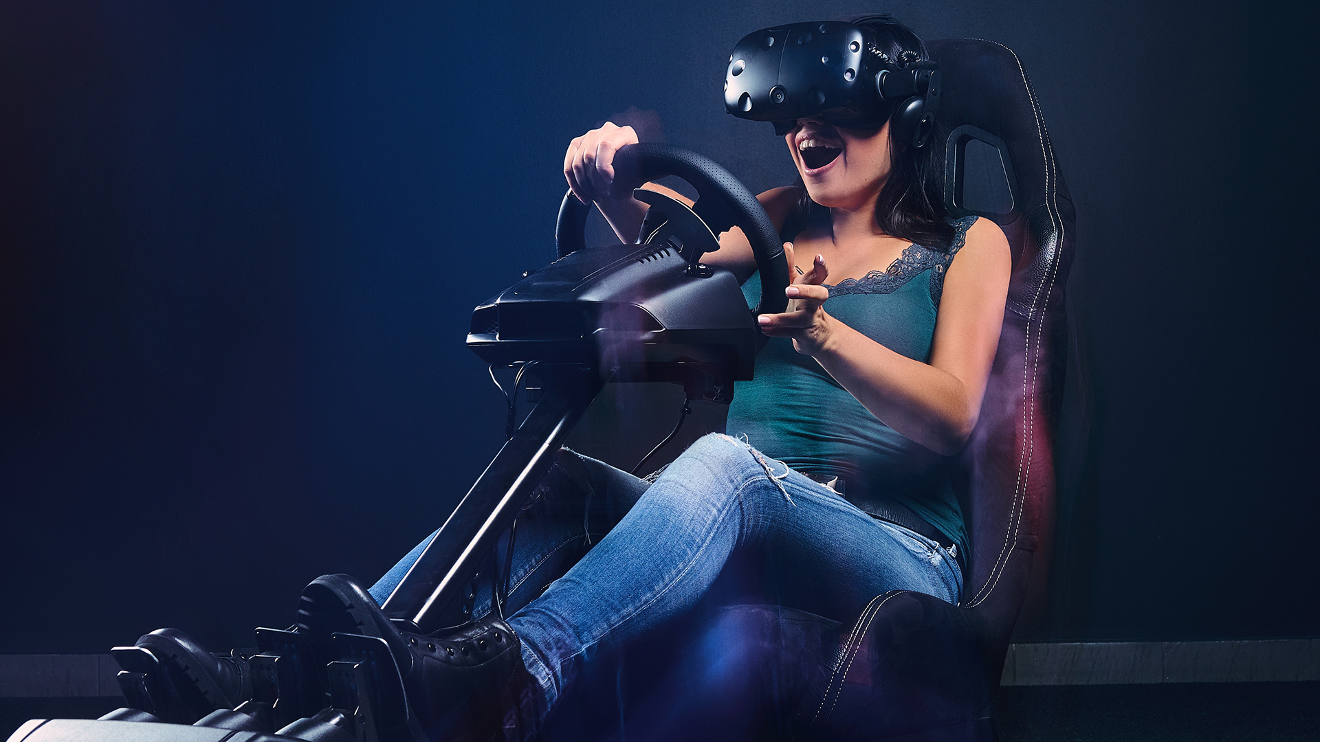 Woman wearing VR headset having fun while driving on car racing simulator cockpit with seat and wheel.