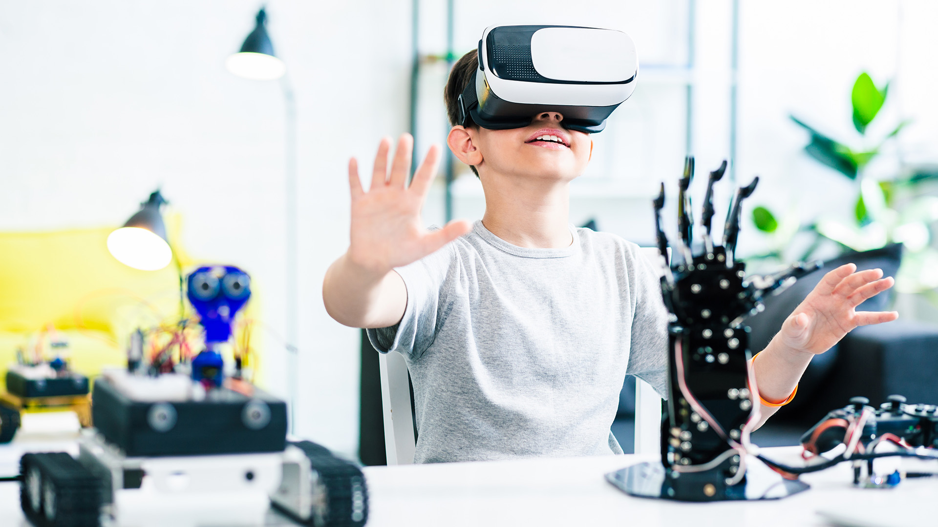 kid is using virtual reality for education and experimenting with robotic devices