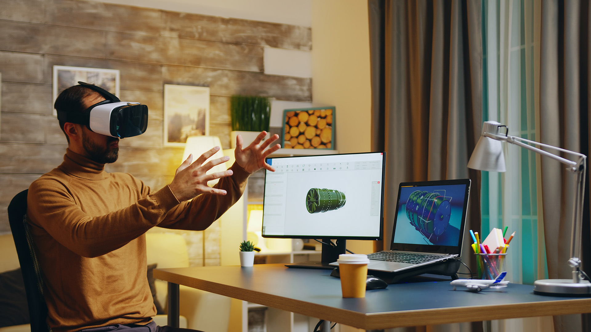 Engineer using virtual reality headset for remote collaboration at his desk at home