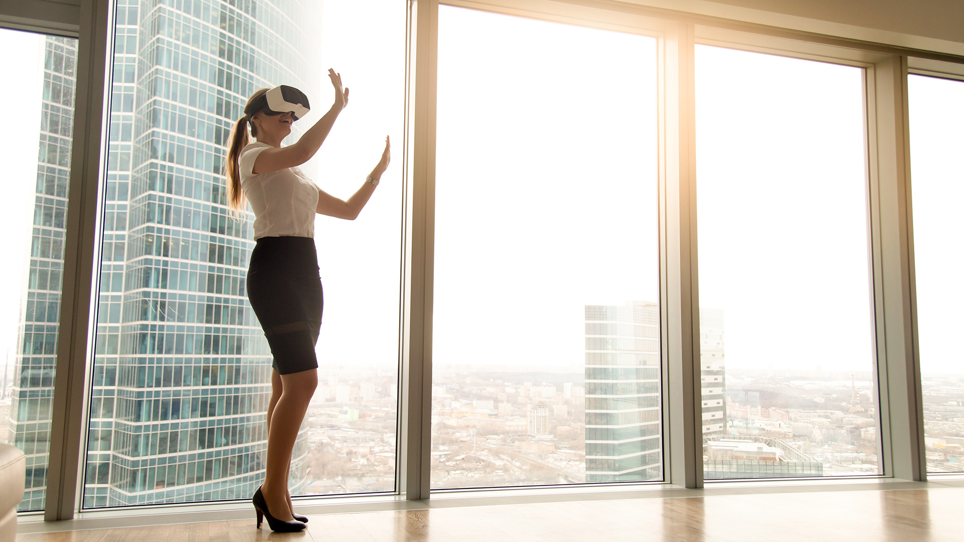 Excited businesswoman wearing headset experiencing real estate virtual tour standing near window