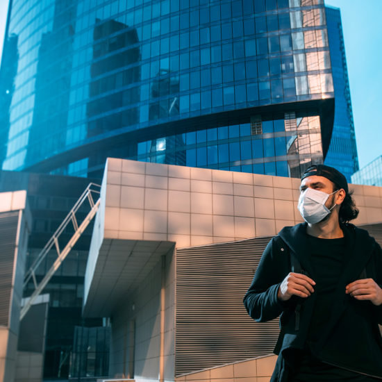 man in medical mask looking away from built environment in a post coronavirus world