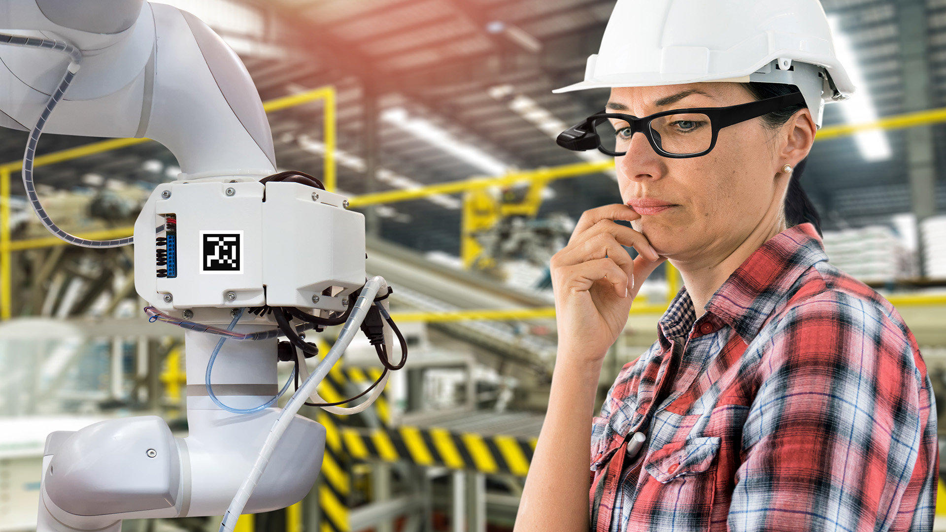 engineer woman wearing ar classes in a factory looking at robot arm