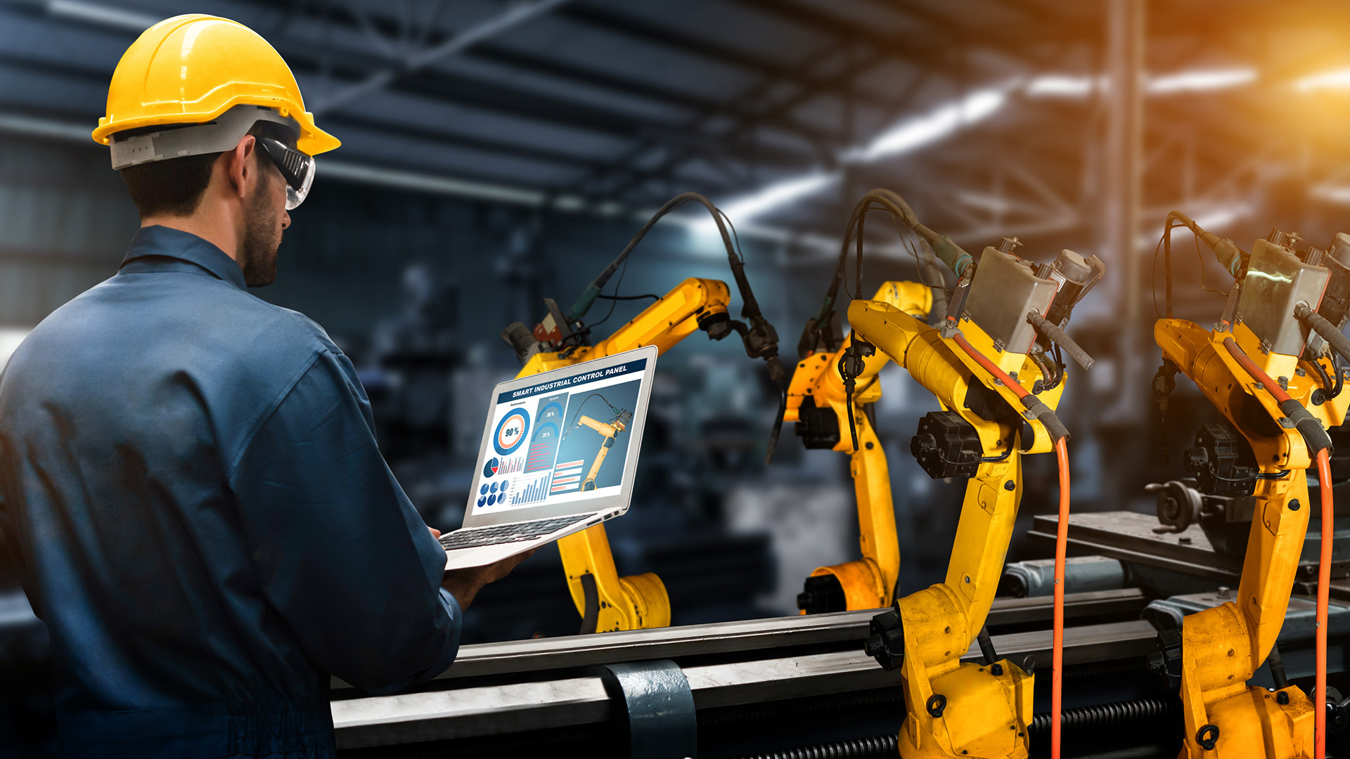 Smart factory engineer using automation technology to control robotic arms on a tablet