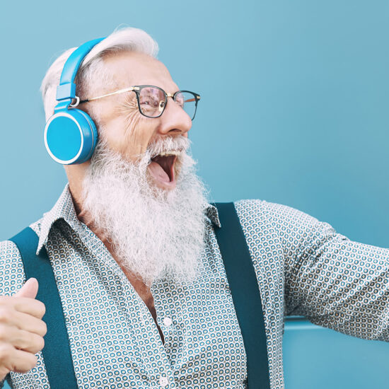 Happy senior male having fun using mobile smartphone playlist apps - technology and elderly lifestyle people concept for digital marketing