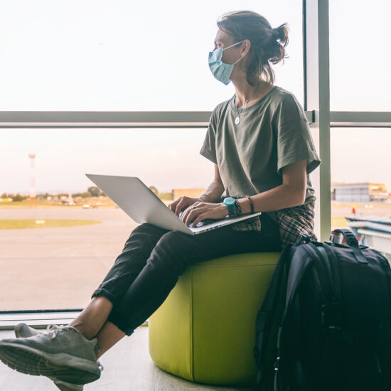 young digital nomad woman wearing a medical mask waiting for her plane at the airport in a post-pandemic world