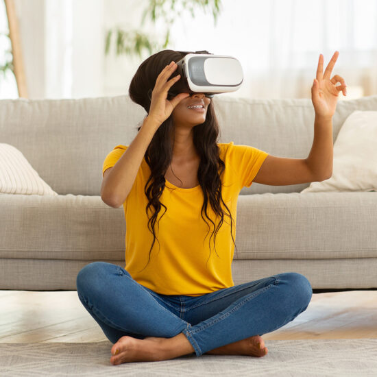 Young black woman in VR headset touching air during virtual reality experience at home during COVID lockdowns