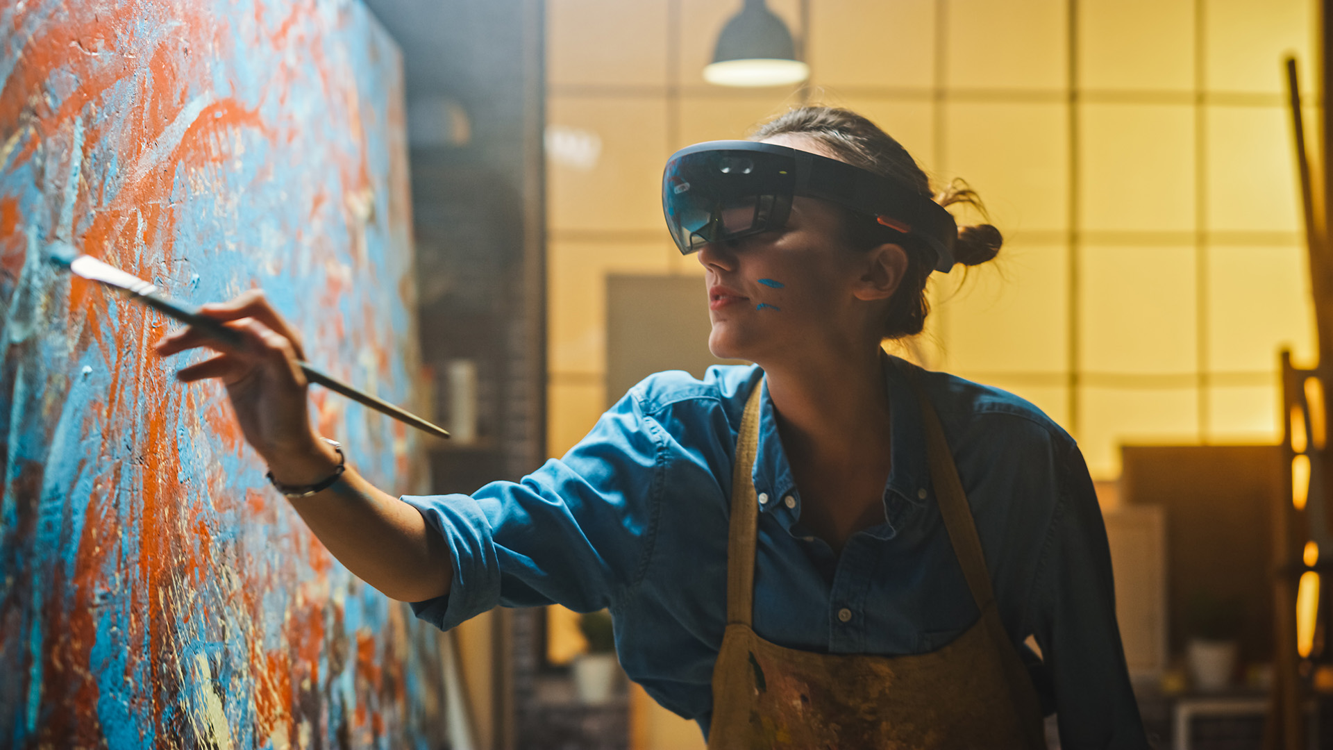 Talented Female Artist Wearing Augmented Reality Headset Working on Abstract Digital Painting, Uses Paint Brush To Create New Concept Art Using Virtual Reality Interface. High tech Creative Modern Studio